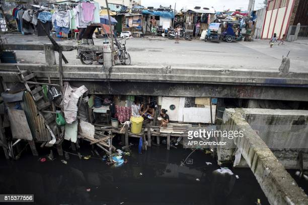 Residents living under a bridge eat lunch at the Estero de Vitas in Manila on July 16 2017 The Philippine economy has sustained one of the fastest...