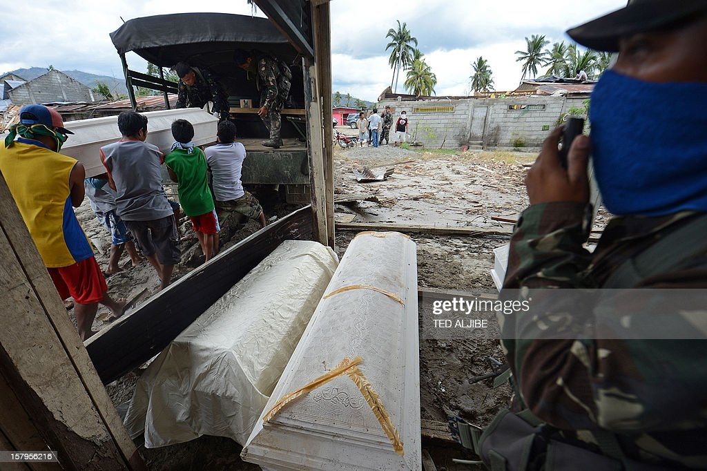 Residents (L) load a coffin into a military truck containing the body of a victim who died in flash flooding caused by Typhoon Bopha, at the old market in New Bataan, Compostela Valley province on December 8, 2012. Hungry and homeless typhoon survivors appealed for help on December 8 as the ravaged southern Philippines mourned its more than 500 dead and desperate people in one hard-hit town looted shops in search of food. AFP PHOTO / TED ALJIBE