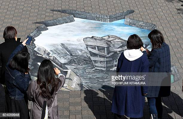 Residents look at a 3D optical illusion artwork of a devastated cityscape in Aleppo Syria at the campus of the Meiji University in Tokyo on November...