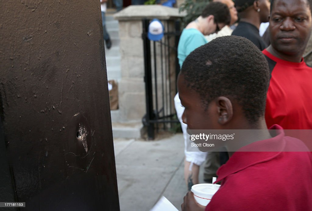 Residents look at a bullet hole in a traffic control box outside the Uptown Baptist Church as they gather for a prayervigil for the people wounded in Monday's shooting on August 21, 2013 in Chicago, Illinois. Five people who were standing in front of the church were shot August 19, when a gunman opened fire from a passing vehicle.