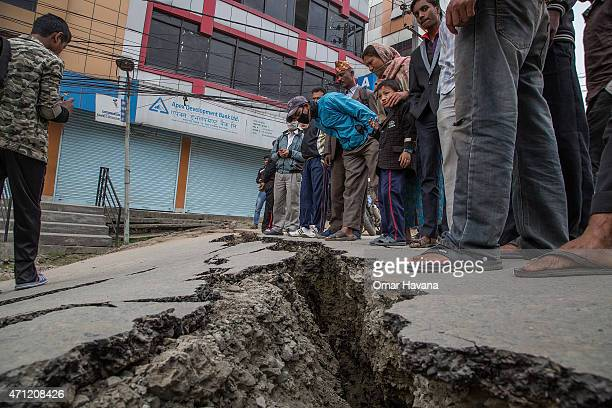 Residents look at a crack in the pavement on April 26 2015 in Kathmandu Nepal A major 78 earthquake hit Kathmandu midday on Saturday and was followed...