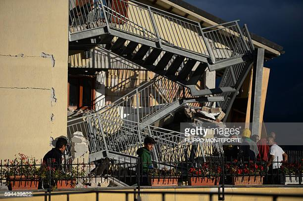 TOPSHOT Residents look at a damaged home after a strong earthquake hit Amatrice on August 24 2016 Central Italy was struck by a powerful 62magnitude...