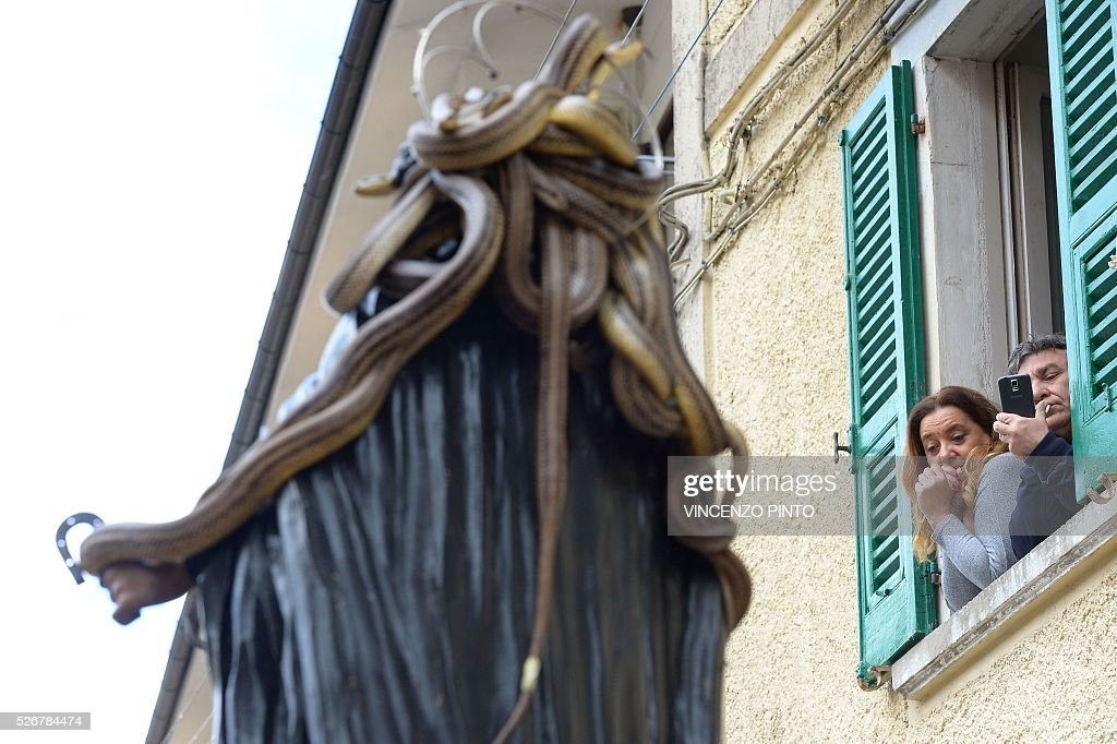 Residents look at a statue of Saint Domenico covered with live snakes during an annual procession in the streets of Cocullo, a small village in the Abruzzo region, on May 1, 2016.