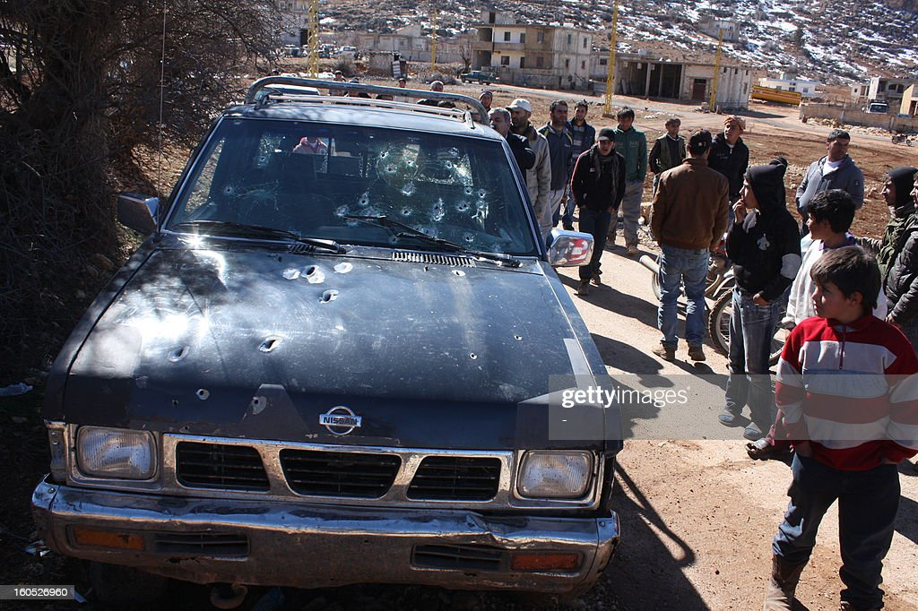 Residents look at a vehicle covered with bullet marks that belonged to a man wanted for several terrorist acts who was hunted the day before by an army patrol in the village of Arsal, on the border with Syria, on February 2, 2013. The army patrol was 'ambushed in Arsal as it hunted' the fugitive and two soldiers were killed in the clash.