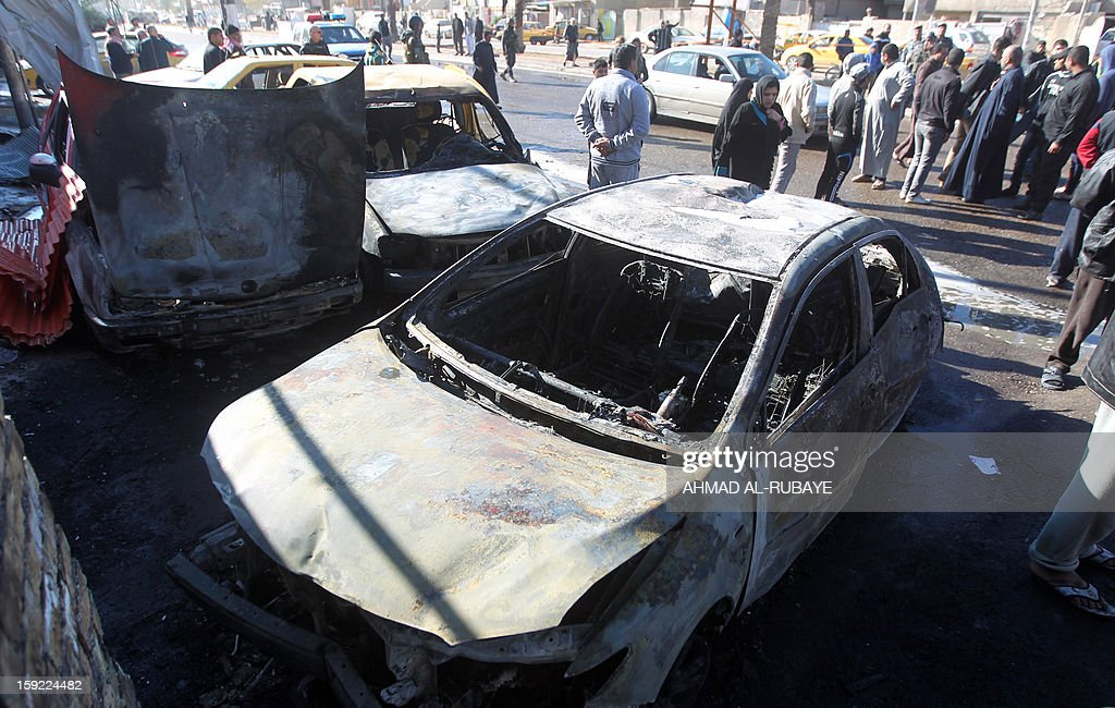 Residents look at burnt cars after a car bomb explosion that killed at least three people and wounded 11 others on January 10, 2013, near a police station in the predominantly Shiite neighbourhood of Hurriyah. The latest violence comes with Iraq mired in a series of interlocking crises that have raised tensions as anti-government protesters have blocked off a key trade route in more than two weeks of ongoing rallies.