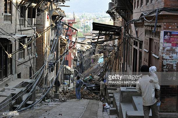Residents look at collapsed houses in Bhaktapur on the outskirts of Kathmandu on April 27 two days after a 78 magnitude earthquake hit Nepal Nepalis...