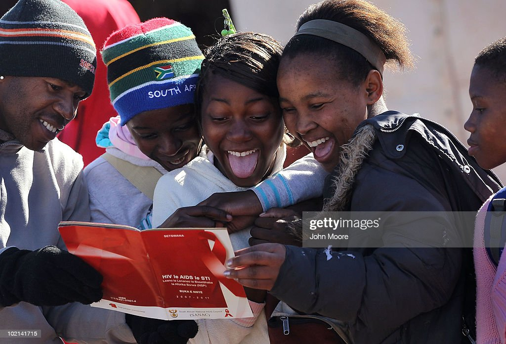 Residents look at HIV/AIDS awareness literature during a soccer match held by the nonprofit Population Services International ahead of a World Cup...