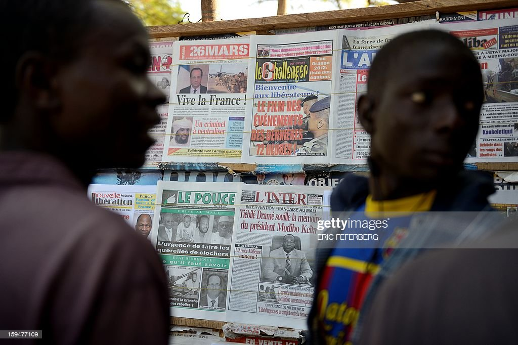 Residents look at newspapers' frontpages focusing on France's military intervention to turn back the terrorist threat in Mali on January 14, 2013 in Bamako.