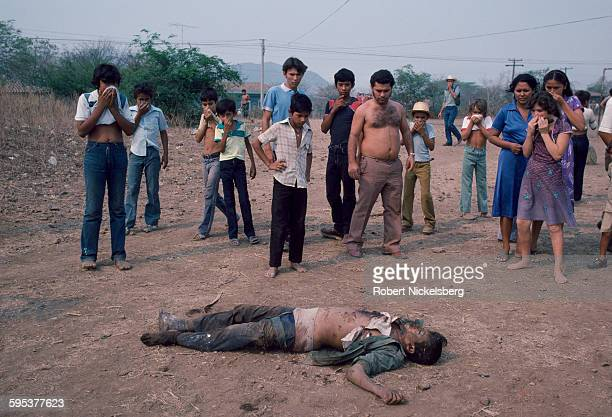 Residents look at the body of an executed man left in a neighborhood on the city outskirts San Salvador El Salvador May 1 1983 At the time the...