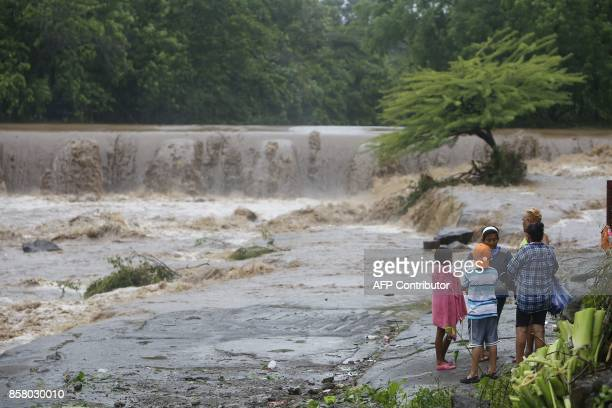 Residents look at the floodings of the Masachapa River following the passage of Tropical Storm Nate in the city of Masachapa about 60km from the city...