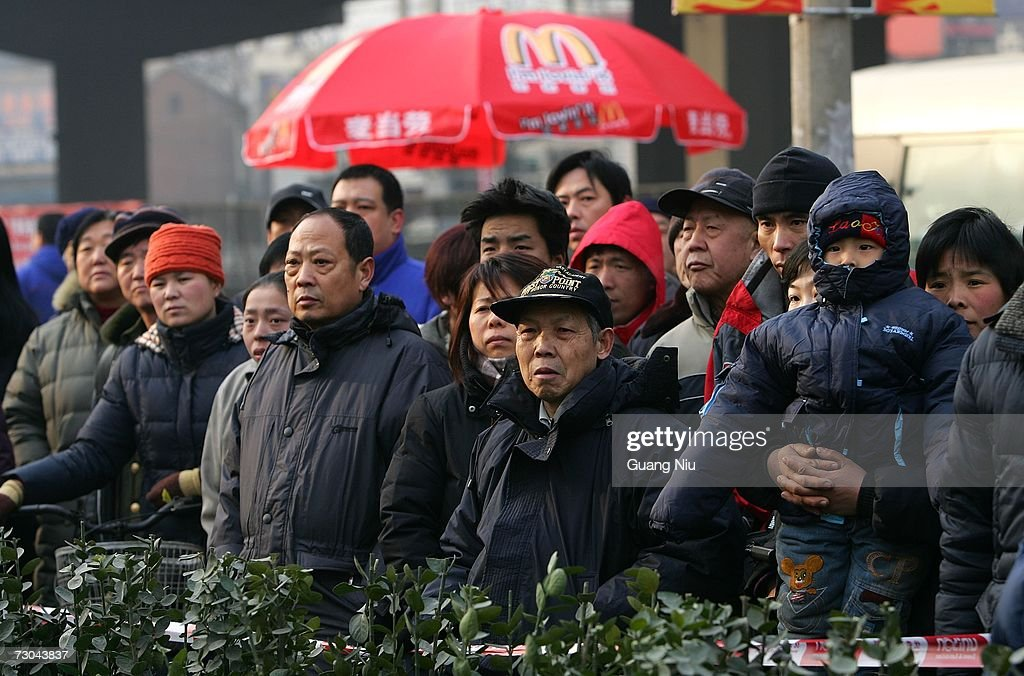 Residents look at the opening ceremony for a new McDonald's drive-thru facility on January 19, 2007 in Beijing, China. McDonald's opened its first restaurant in mainland China in 1990, in Shenzhen, Guangdong province and now operates 760 restaurants countrywide, which employ over 50,000 people.