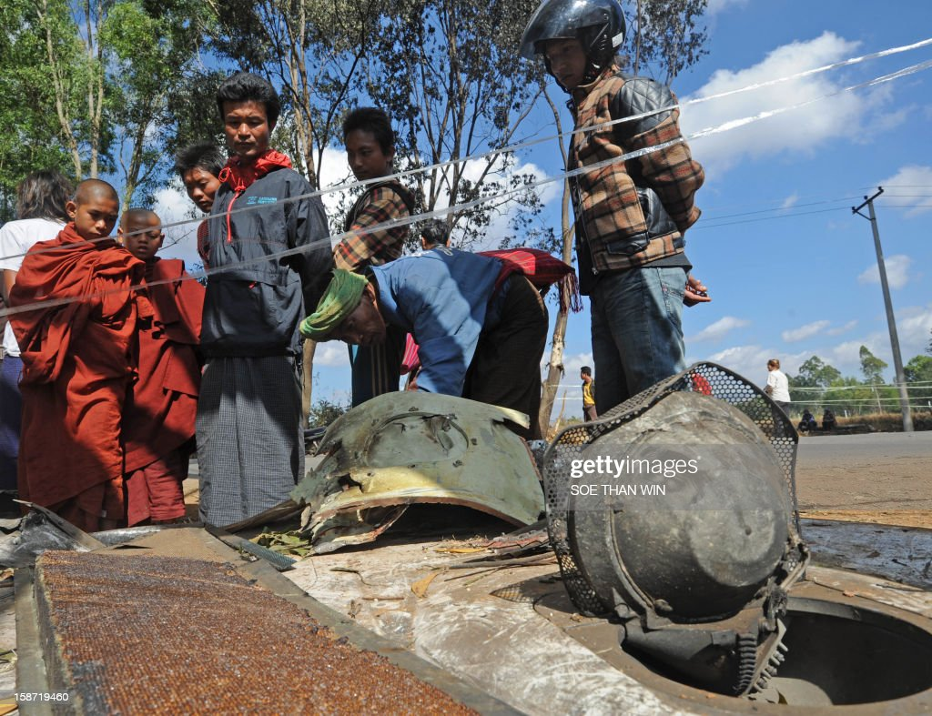 Residents look at the remains of a plane that crash landed the day before near Heho airport in the southern Shan state on December 26, 2012. Myanmar was investigating the cause of an air accident that left two people dead and 11 injured when a passenger jet packed with foreign tourists crash-landed and caught fire. AFP PHOTO/Soe Than WIN