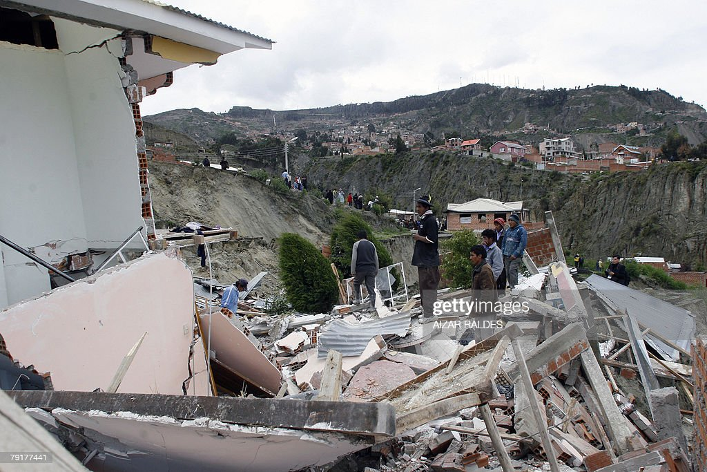 Residents look at the remains of their house 23 January, 2008 in Alpacoma valley in La Paz, after heavy rains caused a landslide that devastated 11 houses. The Bolivian government decreed on Tuesday a national emergency to counteract damages caused by heavy rains and floods battering the country since last November. According to official sources, 22 people died so far and about 20,000 families have been damaged.