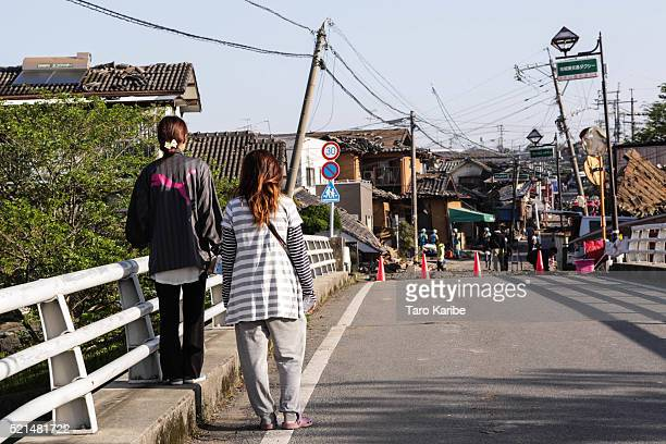 Residents look back upon homes destroyed by a recent earthquake on April 16 2016 in Kumamoto Japan Following a 64 magnitude earthquake on April 14th...