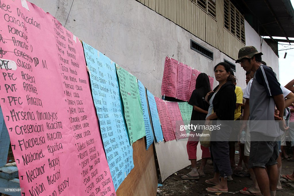 Residents look for the lists of names dead and missing people in flood-hit village brought about by typhoon Bopha in the southern Philippine township of New Bataan, Philippines. More than 500 people have been killed and scores of others remain missing after Typhoon Bopha, the strongest storm to hit the Philippines this year, pounded the region.