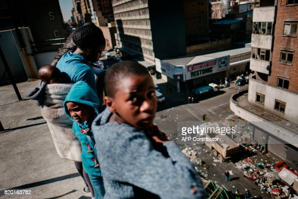 TOPSHOT Residents look from a terrace at municipal workers clearing the belongings of evicted residents of the Fattis Mansion in Johannesburg on July...