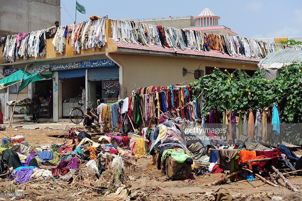 Residents look on as clothes are hung out to dry in the aftermath of floods in Karachi on August 5, 2013. Pakistani disaster relief officials issued fresh flood warnings after the death toll from heavy monsoon rains rose to 45 and waters paralysed parts of the largest city Karachi. Flash floods caused by monsoon downpours have inundated some main roads in the sprawling port city and swept away homes in the northwestern province of Khyber Pakhtunkhwa. AFP PHOTO / RIZWAN TABASSUM