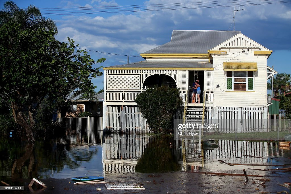 Residents look on as floods suround thier house as parts of southern Queensland experiences record flooding in the wake of Tropical Cyclone Oswald on January 29, 2013 in Bundaberg, Australia.Four deaths have been confirmed and thousands have been evacuated in Bundaberg as the city faces it's worst flood disaster in history. Rescue and evacuation missions continue today as emergency services prepare to move patients from Bundaberg Hospital to Brisbane amid fears the hospital could lose power.