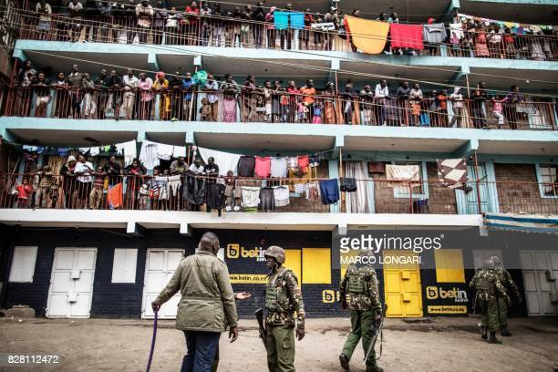 TOPSHOT Residents look on as Kenyan Administration Police officers patrol in the Mathare Slum of Nairobi on August 9 during protests against Kenya's...