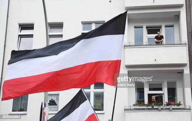 Residents look on as NeoNazis march with the original German Reich flag the same colors as the banned Nazi flag at an extreme rightwing demonstration...