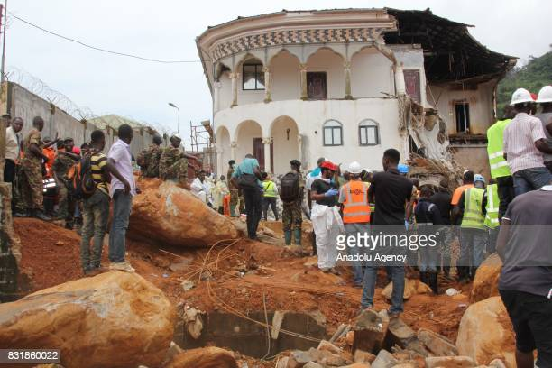 Residents look on as workers remove a wreckage at Regent region of Freetown after landslide struck the capital of the west African state of Sierra...