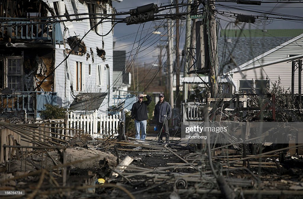 Residents look over the damage in the Breezy Point neighborhood of the Queens borough of New York, U.S., on Wednesday, Oct. 31, 2012. Atlantic superstorm Sandy may cut U.S. economic growth as it keeps millions of employees away from work and shuts businesses from restaurants to refineries in one of the nationís most populated and productive regions. Photographer: Scott Eells/Bloomberg via Getty Images