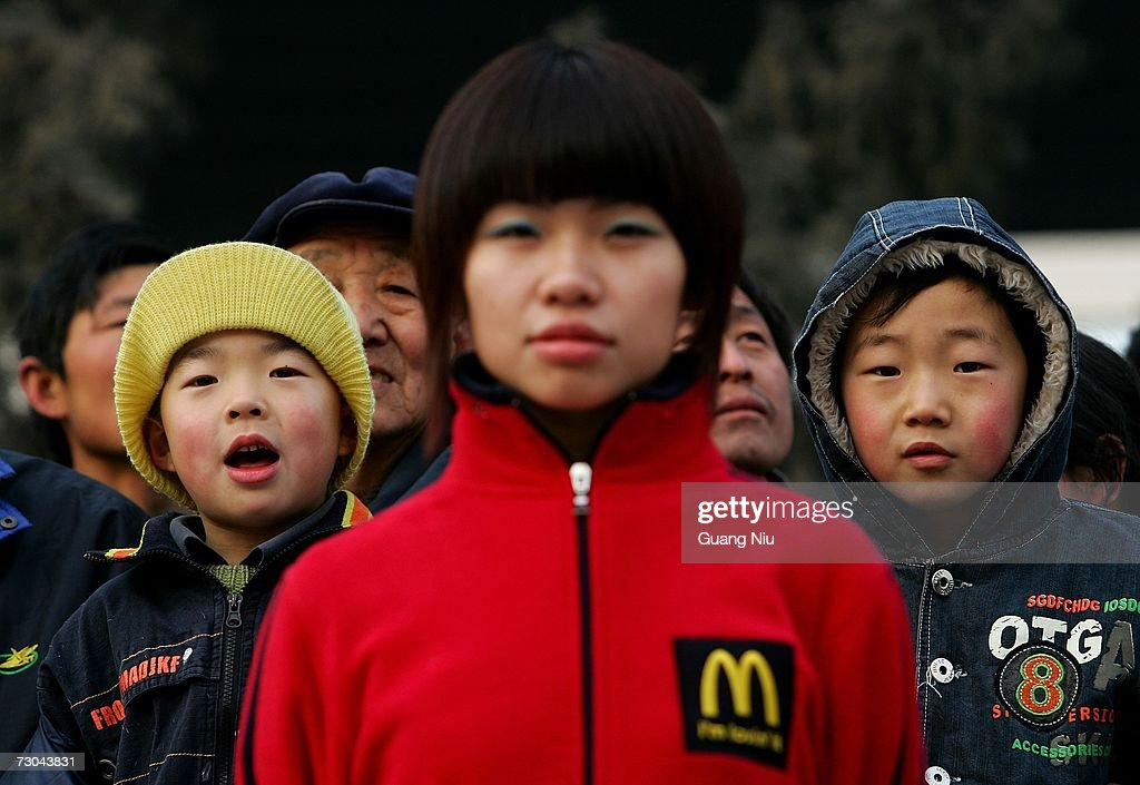 Residents look past a McDonald' employee (C) during the opening ceremony for a new McDonald's drive-thru facility on January 19, 2007 in Beijing, China. McDonald's opened its first restaurant in mainland China in 1990, in Shenzhen, Guangdong province and now operates 760 restaurants countrywide, which employ over 50,000 people.