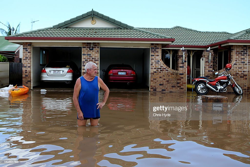 A residents looks at the damage to his street as parts of southern Queensland experiences record flooding in the wake of Tropical Cyclone Oswald on January 30, 2013 in Bundaberg, Australia. Flood waters peaked at 9.53 metres in Bundaberg yesterday and began receding overnight, as residents and relief teams prepare to clean-up debris. Four deaths have been confirmed in the Queensland floods and the search is on for two men though to be missing in floodaters in Gatton.
