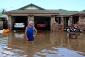 A residents looks at the damage to his street as parts of southern Queensland experiences record flooding in the wake of Tropical Cyclone Oswald on...