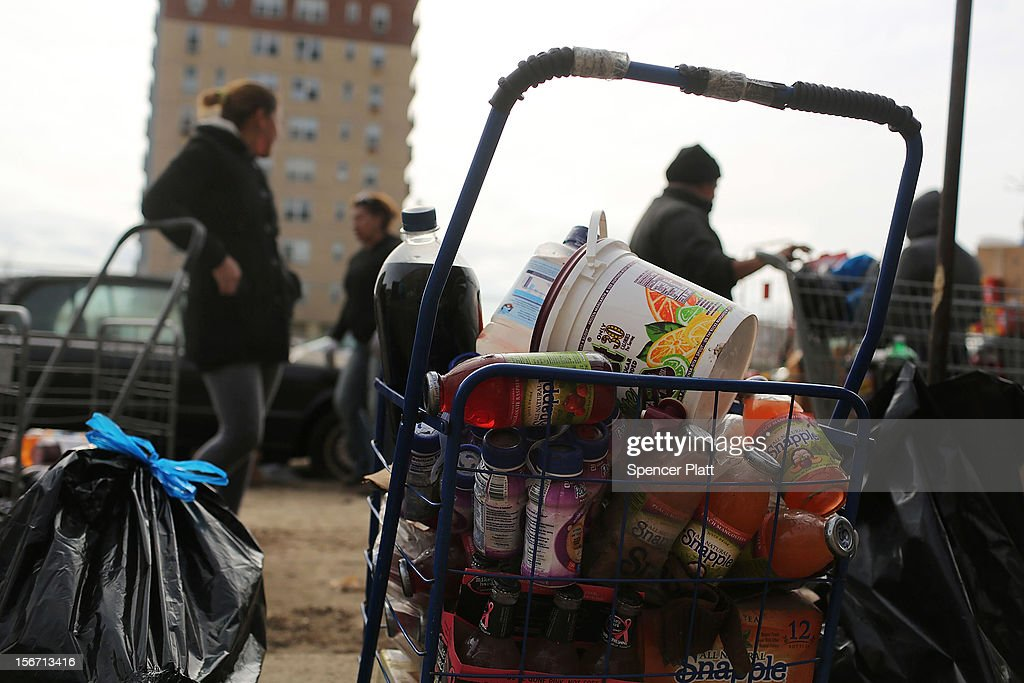 Residents looks through discarded food from a flooded grocery store in the heavily damaged Rockaway neighborhood, where a large section of the iconic boardwalk was washed away on November 19, 2012 in the Queens borough of New York City. Three weeks after Superstorm Sandy slammed into parts of New York and New Jersey, thousands are still without power and heat.