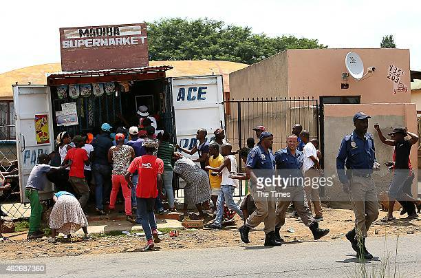 Residents looting a shop owned by foreign nationals on January 22 2015 in Soweto South Africa The looting of shops owned by foreign nationals has...