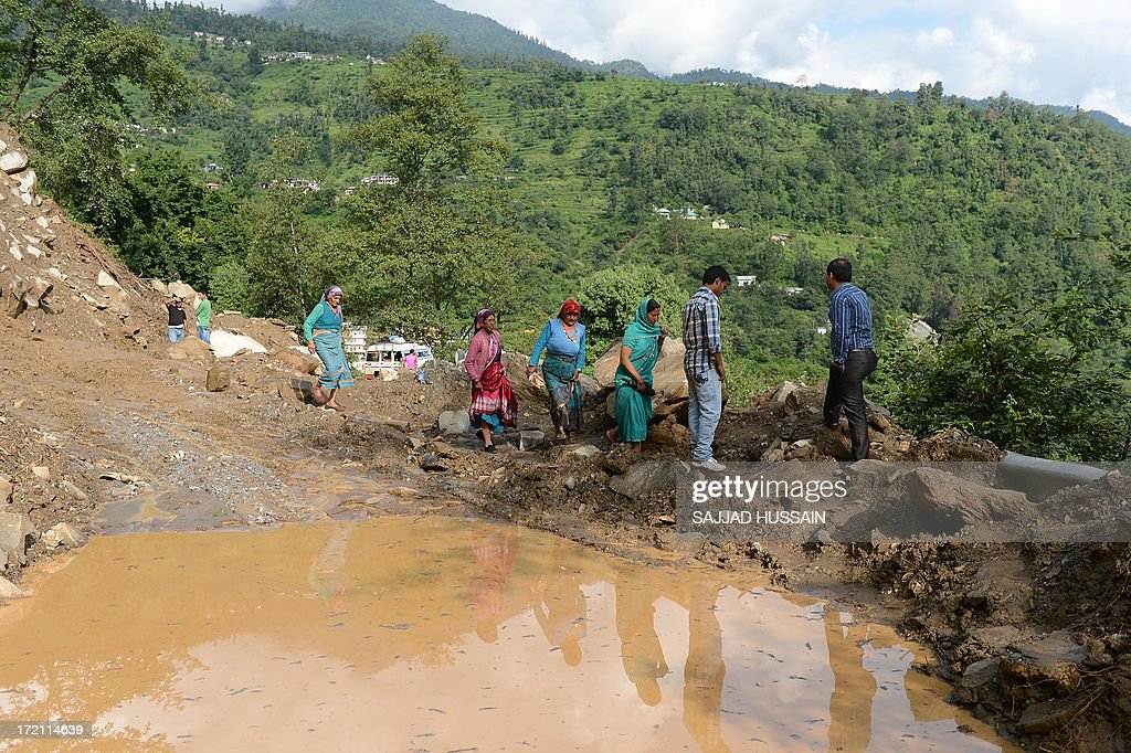 Residents make their way along a damaged roadway to Sonprayag on July 2, 2013, in a flood affected area of the northern Indian state of Uttrakhand. Construction along river banks will be banned in a devastated north Indian state amid concerns unchecked development fuelled last month's flash floods and landslides that killed thousands, the state's top official said. The Chief Minister of Uttarakhand, Vijay Bahuguna, also announced that a regulatory body would be set up to scrutinise future construction as the Himalayan state begins the herculean task of rebuilding following the June 15 floods.