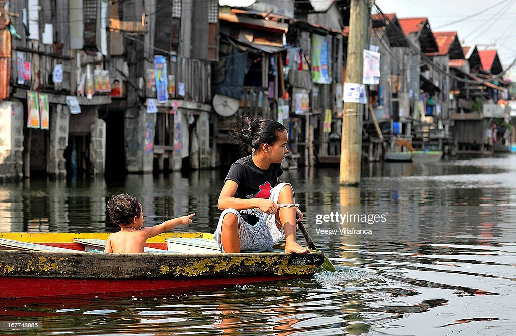 Residents make their way through floodwaters in Artex Compound in Malabon City on April 28, 2013 in Manila, Philippines. The residents of the former textile compound had to adjust their daily lives after flood waters submerged their low-lying village in 2004.