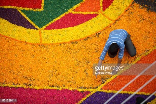 Residents making colourful flower Rangoli on road for immersion celebration of Lord Ganesh, Sangli, Maharashtra, India