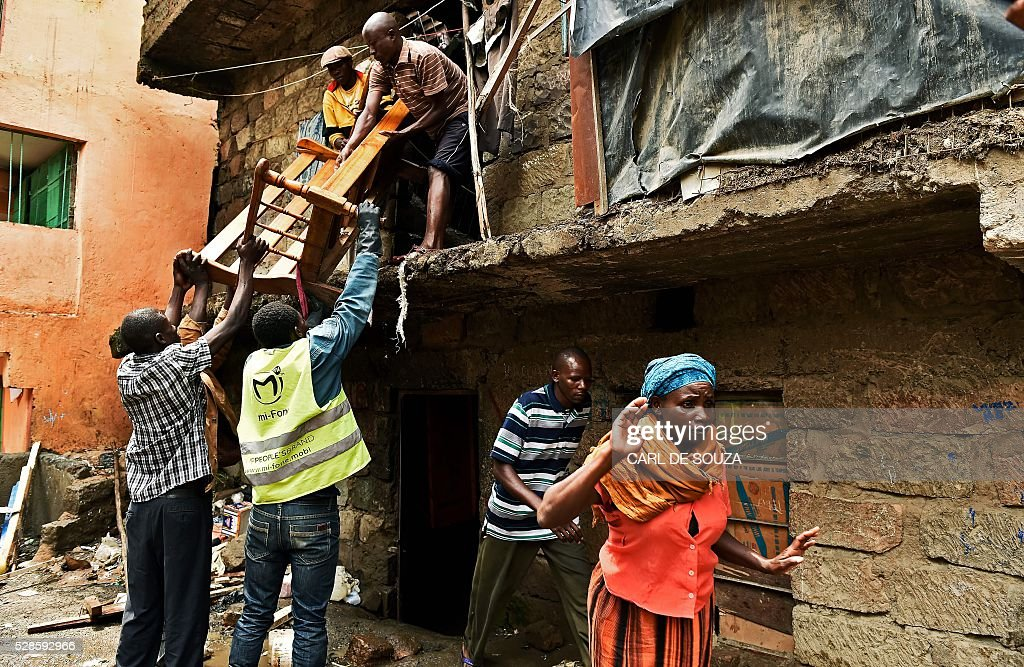 Residents move a sofa frame from a block of flats which is going to be demolished in the in Huruma neighbourhood of Nairobi on May 6, 2016. Following a building collapse which claimed at least 40 lives with more 80 people still unaccounted for, after severe flooding, the government has ordered the demolition of similar unsafe buildings in the area. Located in the poor, tightly-packed Huruma neighbourhood, the building, which housed around 150 families crammed into single rooms, had been slated for demolition after being declared structurally unsound. But an evacuation order for the structure, which was built next to a river just two years ago, was ignored. / AFP / CARL