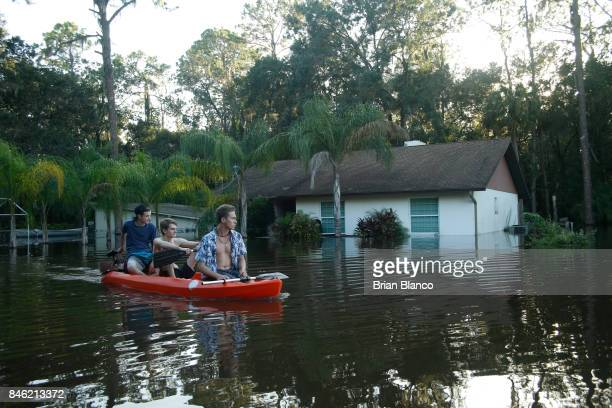 Residents of a nearby neighborhood use a kayak to survey floodwaters from the Alafia River flooding homes in the wake of Hurricane Irma on September...