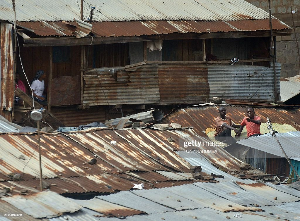 Residents of a neighbouring shanty-town look at from their roof-tops rescuers trying to evacuate a woman earlier discovered still alive on May 05, 2016 after being trapped for six-days in the rubble of a residential house that collapsed during torrential rain in Kenyan capital, Nairobi's low-income suburb of Huruma. The woman was pulled out hours after being located on May 5, 2016 morning by rescuers who gave her oxygen while they continued efforts to extract her from the ruins of the six-storey building. / AFP / TONY