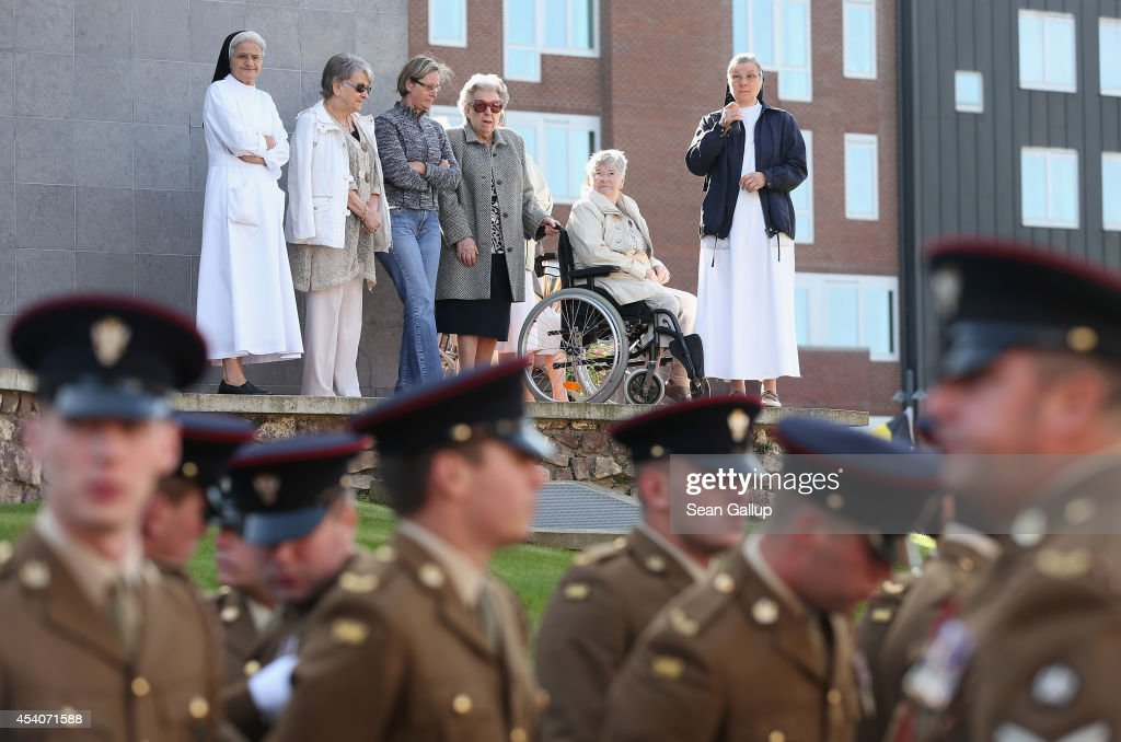 Residents of a senior care home look on as soldiers of the British Mercian Regiment, 1st Battalion, the successor to the Cheshire Regiment, gather before attending a commemoration ceremony at the village cemetery to honour members of the Cheshire Regiment and other soldiers who died fighting the German Army exactly 100 years before during World War I on August 24, 2014 in Audregnies, Belgium. Of the 25 officers and 925 men of the 1st Battalion, Cheshire Regiment who fought that day only a total of 207 would survive after two messengers with instructions for the unit to retreat failed to make it through. The battle came on the heals of the Battle of Mons the day before, which was the first major engagmement between British and German forces in the war. The British, French and Belgian armies were forced to continue their retreat until weeks later, when only a short distance from Paris they managed to reverse the tide of the war and push the Germans back north.