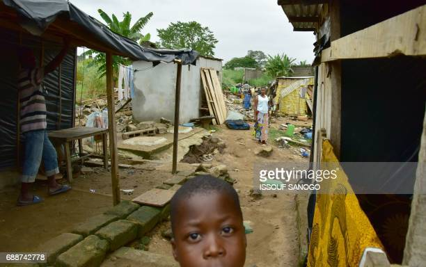 Residents of a shanty town in Abidjan sort through the remains of their homes on May 26 2017 in Abidjan following the death of 5 individuals at the...