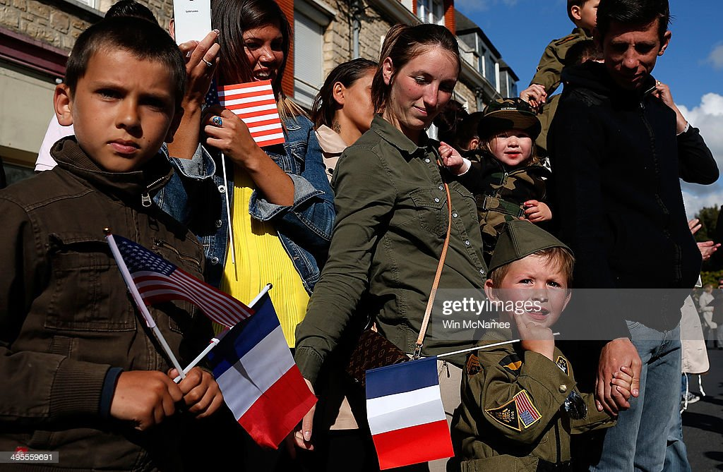 Residents of Carentan watch a military parade marking the week of D-Day June 4, 2014 in Carentan, France. June 6th is the 70th anniversary of the D-Day landings which saw 156,000 troops from the allied countries including the United States and the United Kingdom join forces to launch an attack on the beaches of Normandy, these assaults are credited with the eventual defeat of Nazi Germany. A series of events commemorating the 70th anniversary is planned for the week with many heads of state travelling to the famous beaches to pay their respects to those who lost their lives.