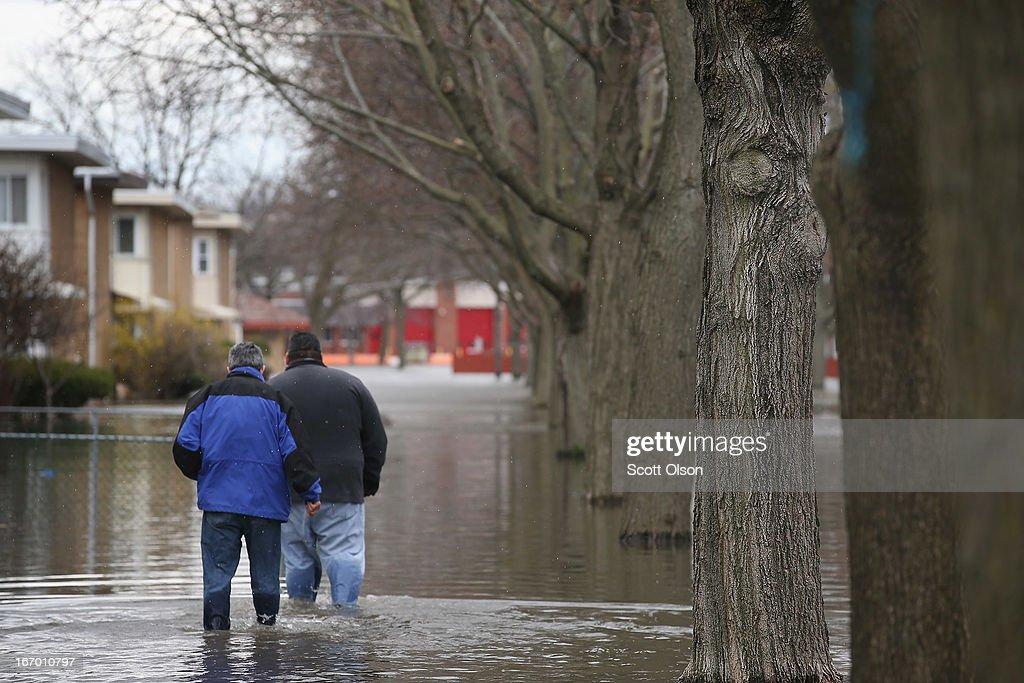 Residents of Des Plaines walk down a flooded sidewalk on a residential street April 19, 2013 in Des Plaines, Illinois. The suburban Chicago town is battling floodwater from the Des Plaines River which is expected to crest at a record 11 feet later today. Record-setting rains and rising rivers have caused wide-spread flooding in many Illinois communities.