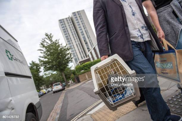 Residents of Dorney tower block on the Chalcots Estate leave their flat carrying their cat and other belongings in bags on June 26 2017 in London...