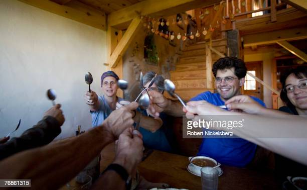 Residents of EcoVillage at Ithaca put their soup spoons together in a communal gesture before beginning their dinner which includes organic...