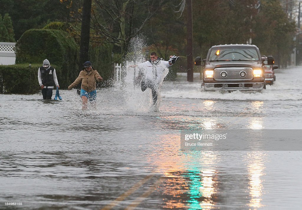 Residents of Freeport make their way up Guy Lomardo Avenue as high tide and winds from Hurricane Sandy combine to flood the steets on October 29, 2012 in Freeport, New York.The storm, which threatens 50 million people in the eastern third of the U.S., is expected to bring days of rain, high winds and possibly heavy snow.