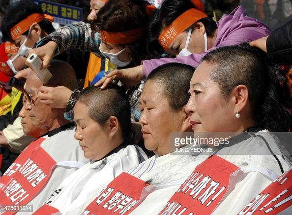 Residents of Icheon City shave their heads near the government building in Seoul 23 February 2007 in protest at the government's refusal to let the...