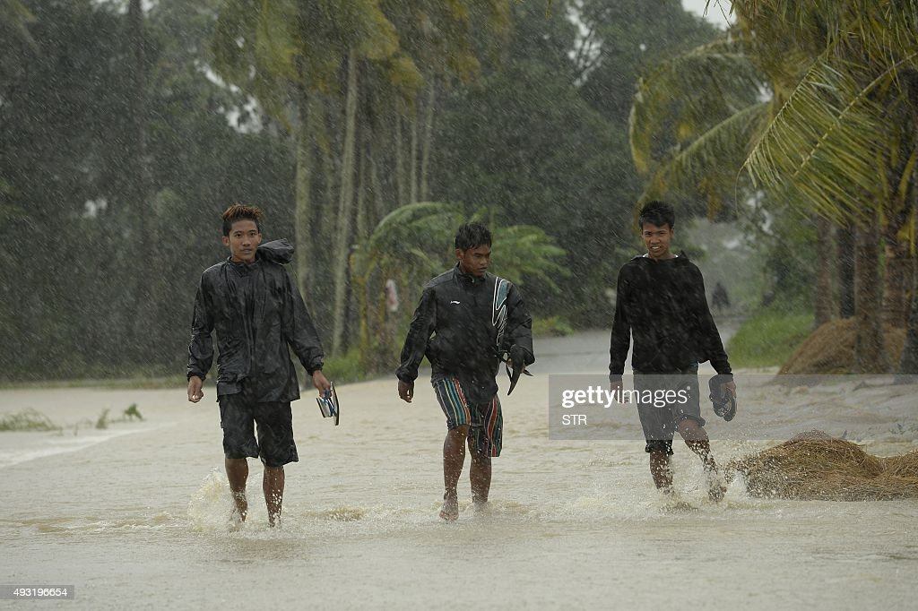 Residents of Ineangan Bambang Nueva Viscaya cross a flooded street after the Magat river swelled caused by typhoon Koppu's continuous rain on October...
