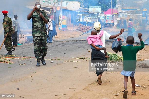 Residents of Kasubi suburb west of Kampala raise their hands as they walk past riot policemen on September 11 2009 in Kampala after riots rocked the...