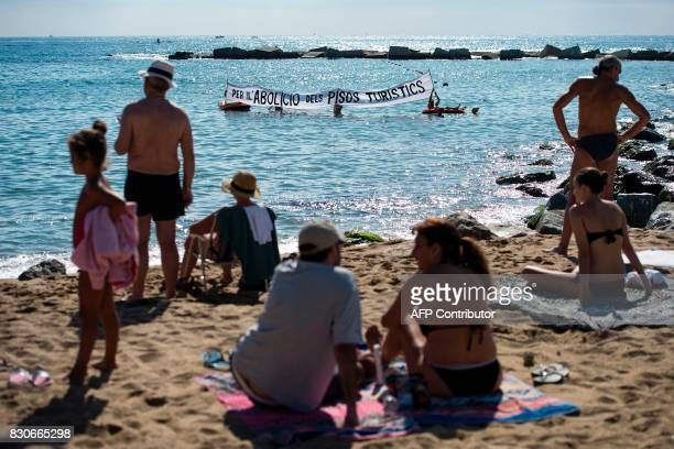 Residents of La Barceloneta neighbourhood hold up a banner reading 'For the abolition of tourist apartments' as they protest against 'drunken...