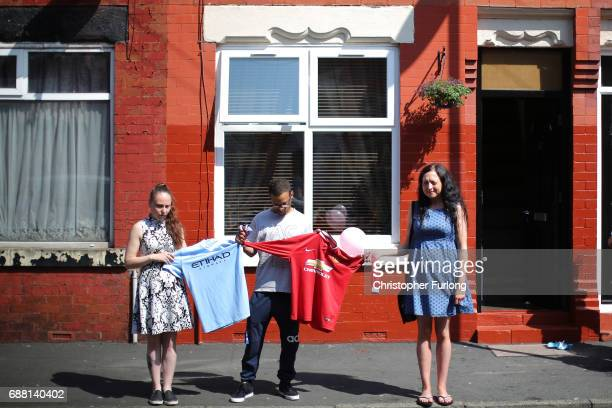 Residents of Lindum Street Moss Side hold Manchester City and Manchester United football shirts as they observe a minutes silence in memory of the...