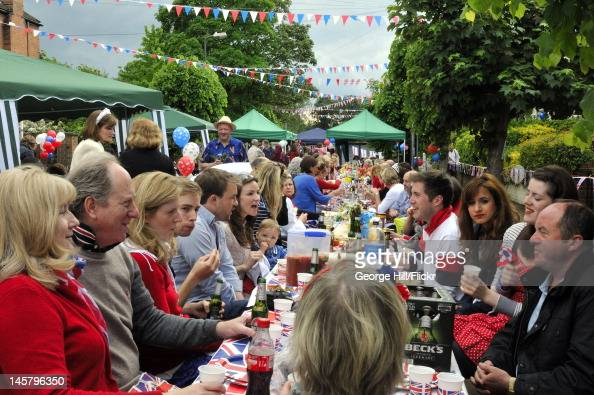 Residents of Melbourne Road Wimbledon South West London are seated at a long unionjack bedecked table enjoying food drink and conversation during...